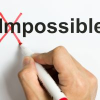 Hand holding marker pen to cross out the word impossible to reveal possible