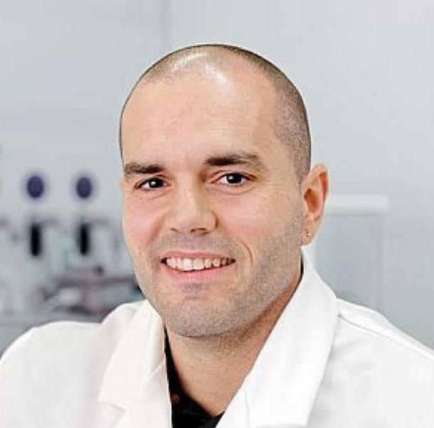 A photograph of Josep Puigmartí-Luis, wearing a white lab coat