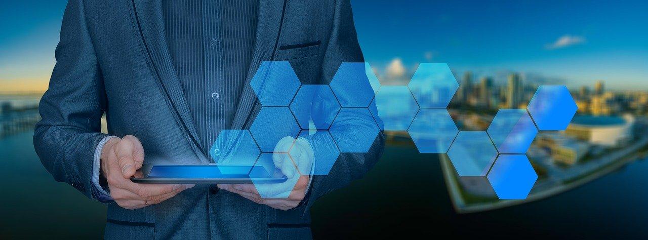 Empresari subjecta una tablet d'on apareix un dibuix amb hexàgons