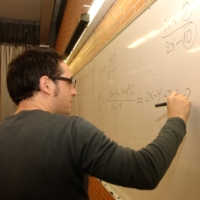 Photograph of a lecturer writing on a board